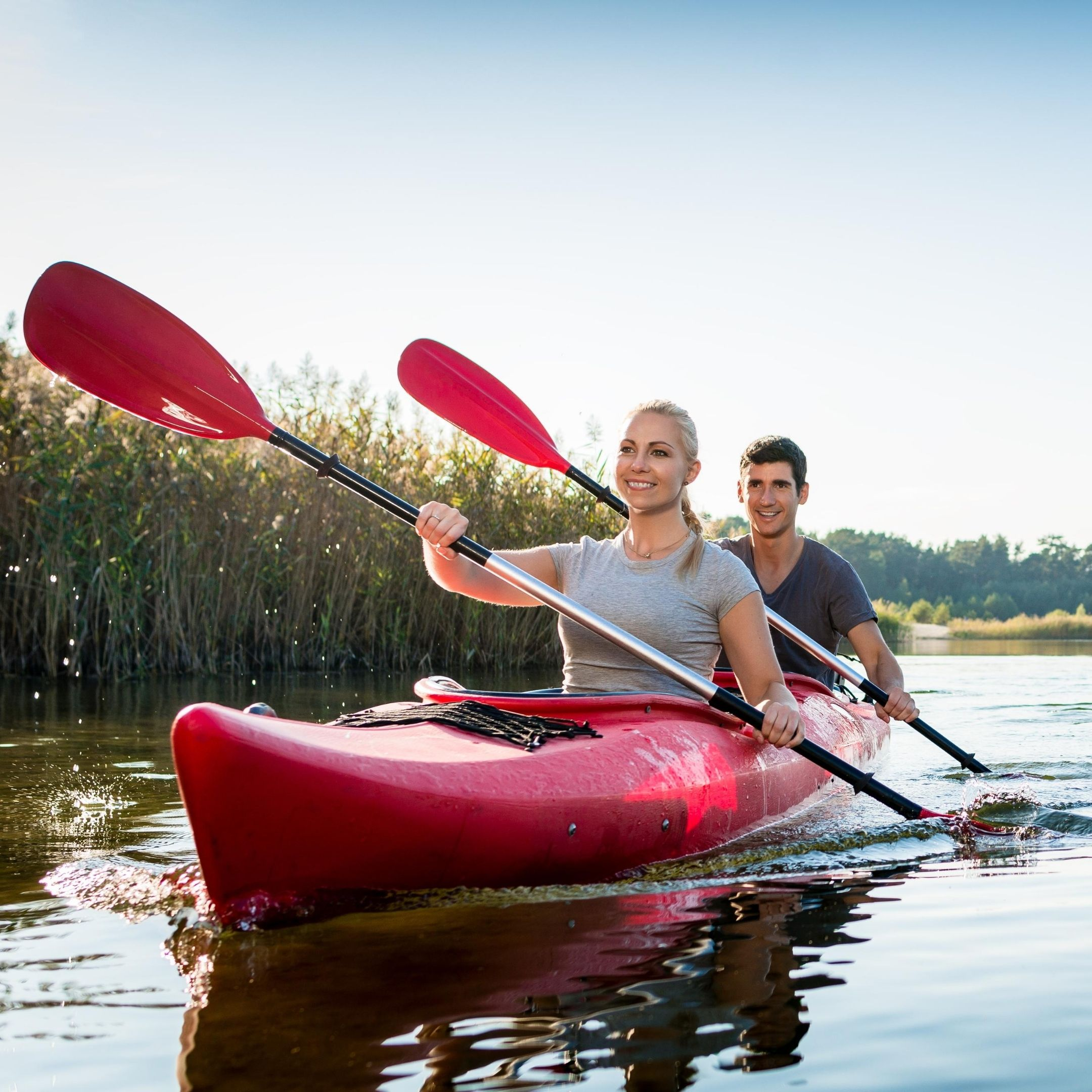 Happy successful couple smooth sailing in canoe